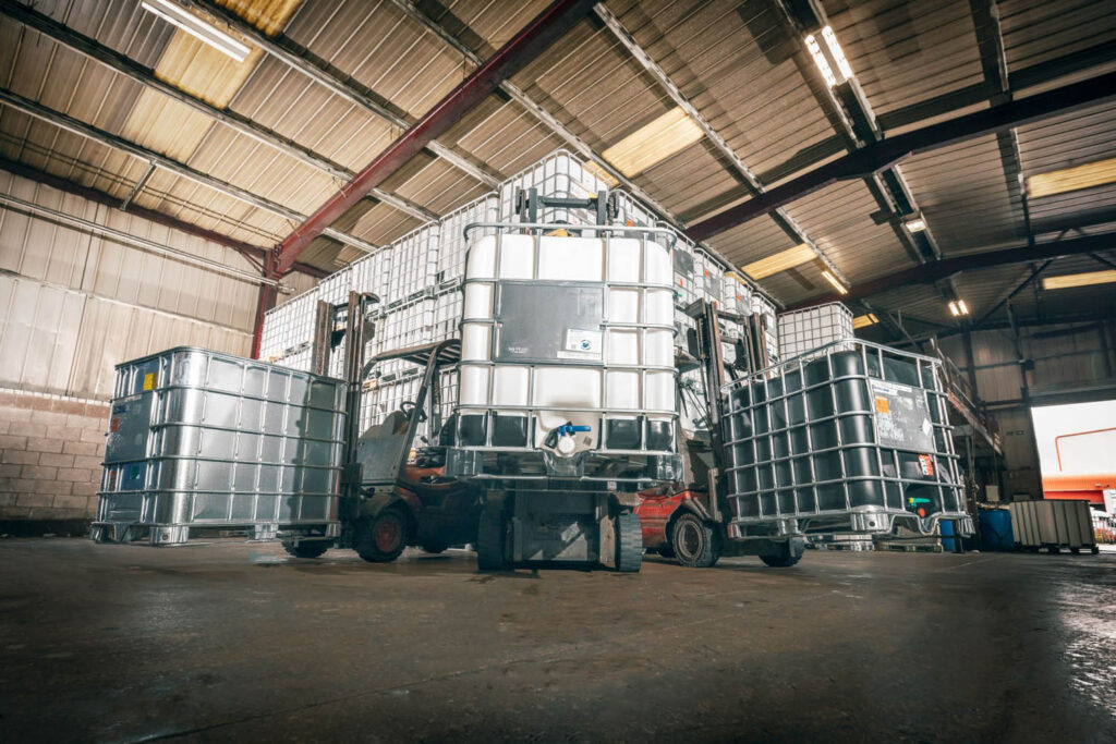 A picture of three forklifts carrying Earthed, Reconditioned and New IBCs at Recontainers Haslingden.