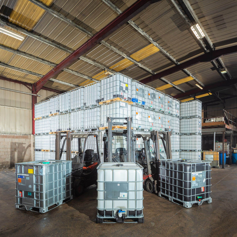 Forklifts in front of rows of wood and metal reconditioned IBCs